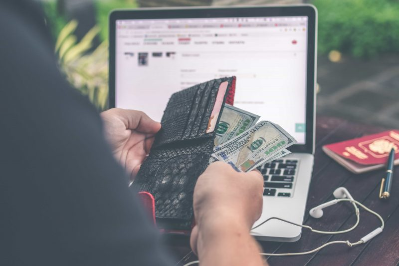 Person counting cash in front of computer